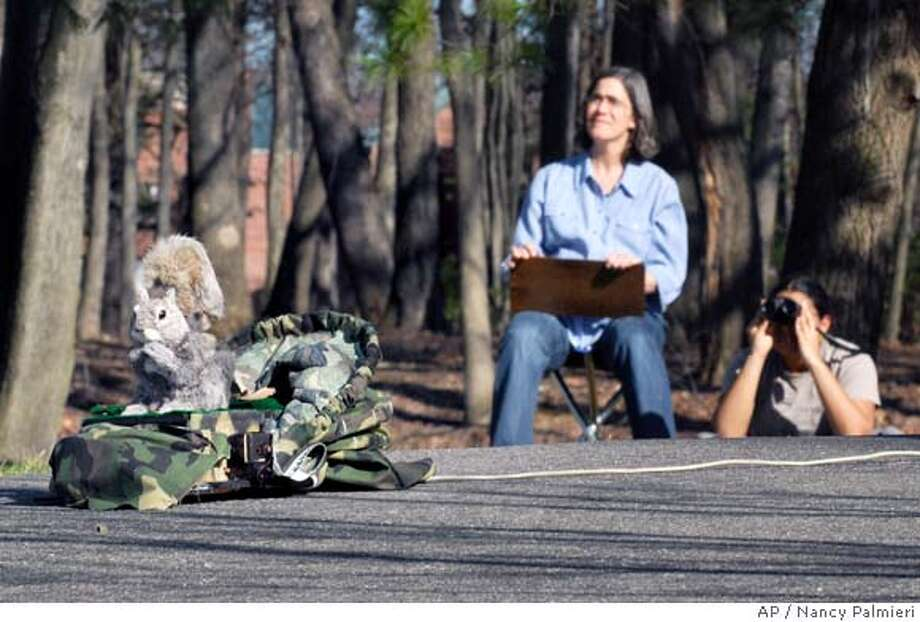 "**ADVANCE FOR USE IN WEEKEND EDITIONS, MAY 3-4, AND THEREAFTER** Rocky, a mechanical ""robo-squirrel,"" at Hampshire College in Amherst, Mass., is shown on duty on the campus Tuesday, April 15, 2008. In back are Sarah Partan, Hampshire assistant professor of animal behavior, left, and student Maya Gounard, 20, spying on real squirrel activity nearby. Rocky is among many robotic critters worldwide letting researchers observe animals in their natural environments rather than in labs. (AP Photo/Nancy Palmieri) Photo: Nancy Palmieri"