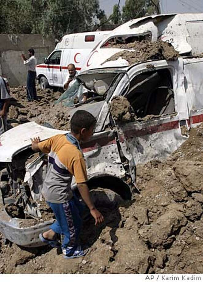 A boy examines an ambulance destroyed in an apparent U.S. airstrike in the Shiite stronghold of Sadr City in Baghdad, Iraq on Saturday, May 3, 2008. More than 100 people were also wounded in clashes Friday and Saturday in Baghdad's embattled Sadr City district, Iraqi health officials said. A U.S. helicopter on Saturday allegedly fired a missile at a target some 50 meters away (yards) from the general hospital in Sadr City, wounding about 28 people and damaging at least seven ambulances, hospital officials said.The U.S. military had no immediate comment about the incident. (AP Photo/ Karim Kadim) Photo: KARIM KADIM