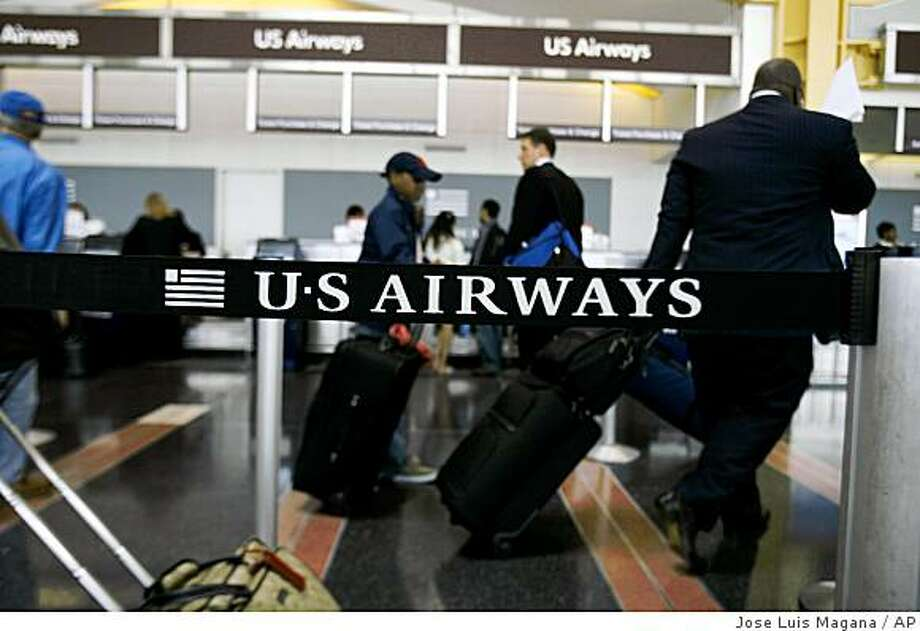 Passengers stand in line to check their luggage at the US Airways counter at Washington's Ronald Reagan National Airport, Thursday, May 1, 2008. Photo: Jose Luis Magana, AP