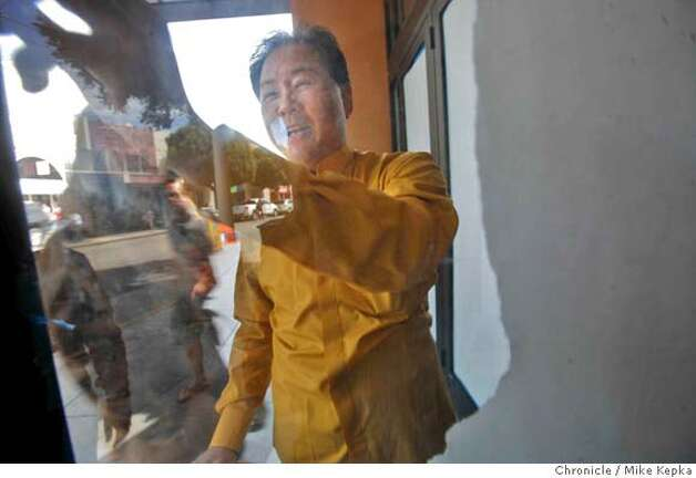 Frank Lee takes down sheets of paper coving the front doors at the Marina Theater on Monday April, 29, 2008 in San Francisco, Calif. The theater, on Chestnut street, is set to open this Friday after after 3 years of preparations.  Photo by Mike Kepka / San Francisco Chronicle Photo: Kepka, Mike