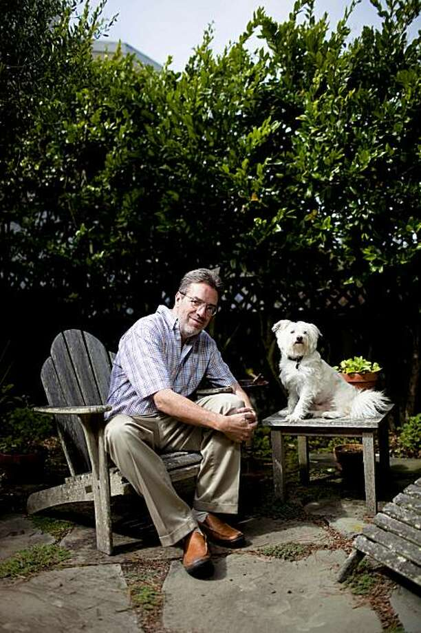 Fiction writer Steven Winn poses for a portrait with his family mutt Como at their home garden in San Francisco, Calif. on Monday, Sept. 14, 2009. A former staff writer at the San Francisco Chronicle, Winn is the author of upcoming book about his comically tumultuous relationship with his dog, which grew out of an ten-part series he penned in the paper. Photo: Stephen Lam, The Chronicle