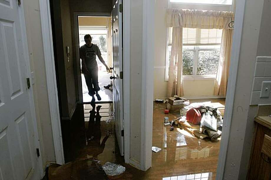A volunteer Eryn Berry walks into a  house to continue clean up efforts after flood waters from Sweetwater Creek receded from it, Wednesday, Sept. 23, 2009, in Austell, Ga. (AP Photo/John Amis) Photo: John Amis, Associated Press