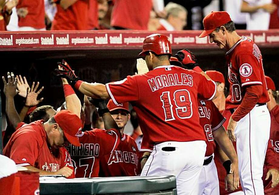 ANAHEIM, CA - SEPTEMBER 28:  Kendry Morales #19 Los Angeles Angels of Anaheim is congratulated by his teammates hitting a two-run home run off pitcher Tommy Hunter of the Texas Rangers during first inning of the baseball game at Angel Stadium on September 28, 2009 in Anaheim, California.  (Photo by Kevork Djansezian/Getty Images) Photo: Kevork Djansezian, Getty Images