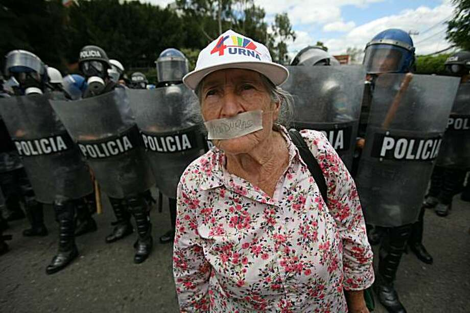 Yolanda Chavarria, 80, with an adhesive tape on her mouth that reads Honduras, stands in front of police officers during a demonstration in support of Hondura's ousted President Manuel Zelaya in Tegucigalpa, Monday, Sept 28, 2009. Honduras' interim government leaders have suspended constitutionally guaranteed civil liberties in a pre-emptive strike against widespread rebellion Monday, three months to the day since they ousted Zelaya in a military-backed coup. (AP Photo/Rodrigo Abd) Photo: Rodrigo Abd, AP