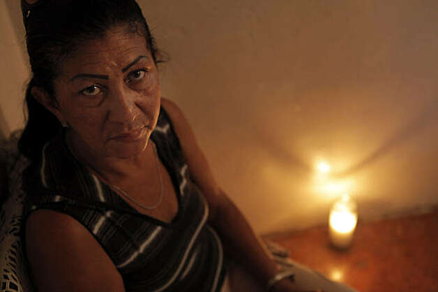 Eufemia Velete, the mother of murder victim, Mario Velete, sits in her house with a candle she keeps lit in memory of her son. Photo: Carlos Avila Gonzalez, The Chronicle