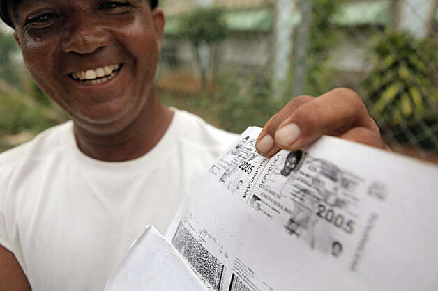 Hochi Leandro Nolasco smiles as he remembers his star player, Angel Villalona, and shows off the registration documents when Angel joined his baseball academy. Photo: Carlos Avila Gonzalez, The Chronicle
