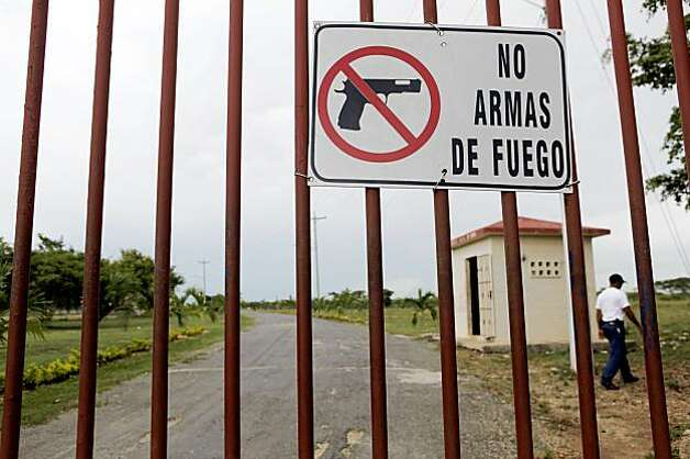 A sign forbids firearms at one of the Major League Baseball training facilities in Bocachica, Dominican Republic. Many of the players carry weapons outside of the playing field, and when tempers flair, the proximity of a weapon only serves to escalate violence. Photo: Carlos Avila Gonzalez, The Chronicle