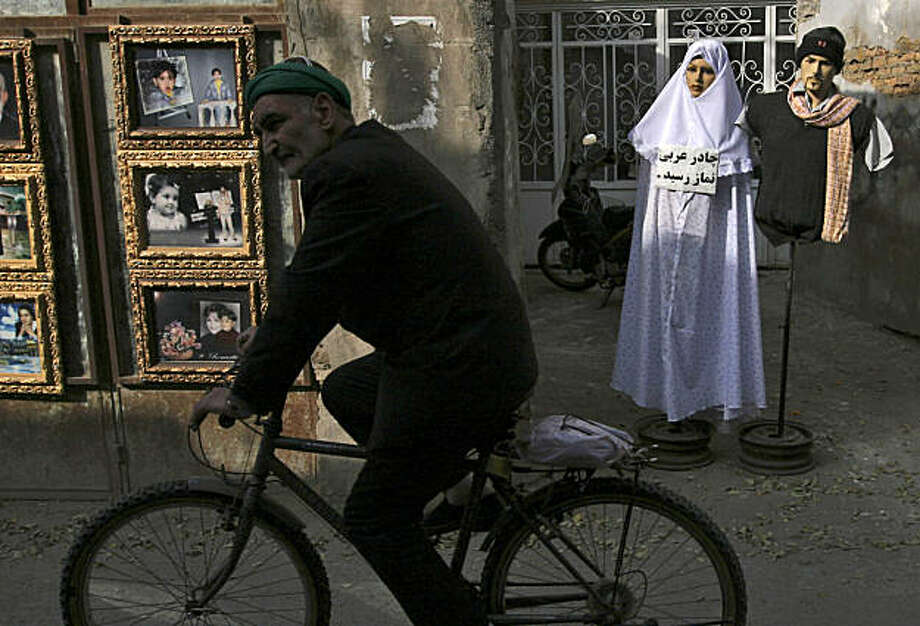 """FILE - In this Friday, Nov. 28, 2008 file photo, an Iranian Muslim man rides his bicycle as he passes unidentified photos of pilgrims, left, and a mannequin at right with a sign in Farsi reading """"Arabian chador (muslim women's veil) for praying is available to buy"""", in Mashhad, Iran. Iranian police warned shop owners Wednesday against displaying female mannequins wearing underwear or showing off their curves amid a government campaign against Western influence. (AP Photo/Hasan Sarbakhshian, File) Photo: Hasan Sarbakhshian, AP"""
