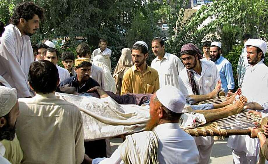People unload a dead body, center covered with sheet, and a badly injured victim of a militant attack at a local hospital in Bannu, Pakistan on Thursday, Sept. 24, 2009. Militants ambushed a convoy of prominent anti-Taliban tribal elders in volatile northwest Pakistan on Thursday, spraying their cars with gunfire, killing several people and wounding a handful of others. (AP Photo/Ijaz Mohammad) Photo: Ijaz Mohammad, AP