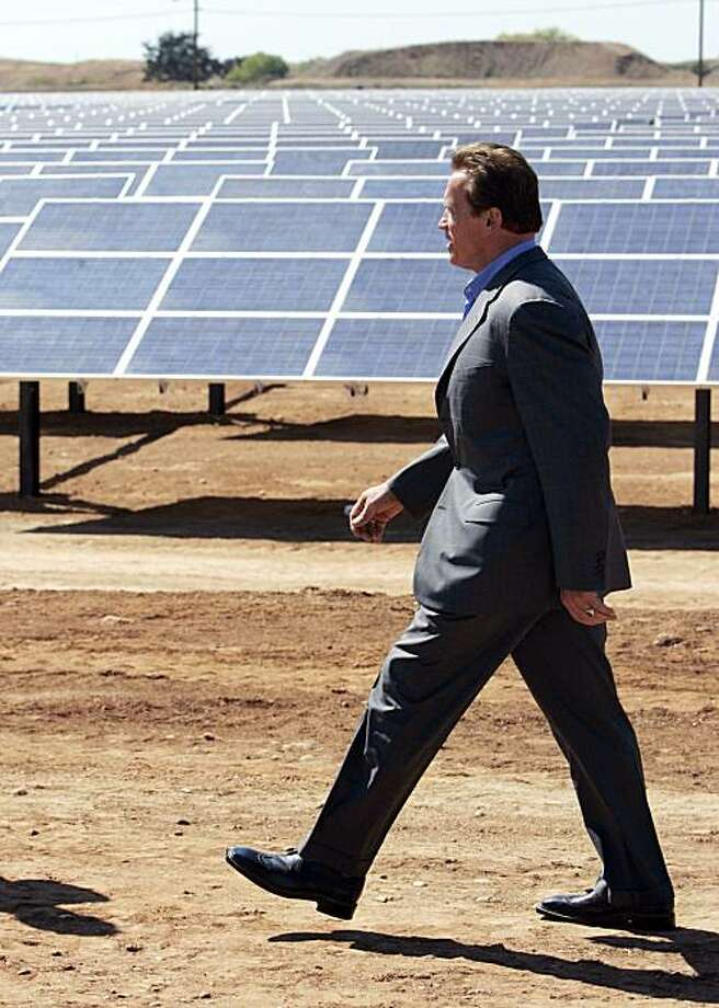 Gov. Arnold Schwarzenegger passes a solar energy field to sign an executive order he signed giving California the nation's most aggressive energy standards, during ceremonies held at  a solar energy field in Rancho Cordova, Calif., Tuesday, Sept. 15, 2009. The order requires utilities to get a third of their power from renewable sources by 2020.(AP Photo/Rich Pedroncelli) Photo: Rich Pedroncelli, AP