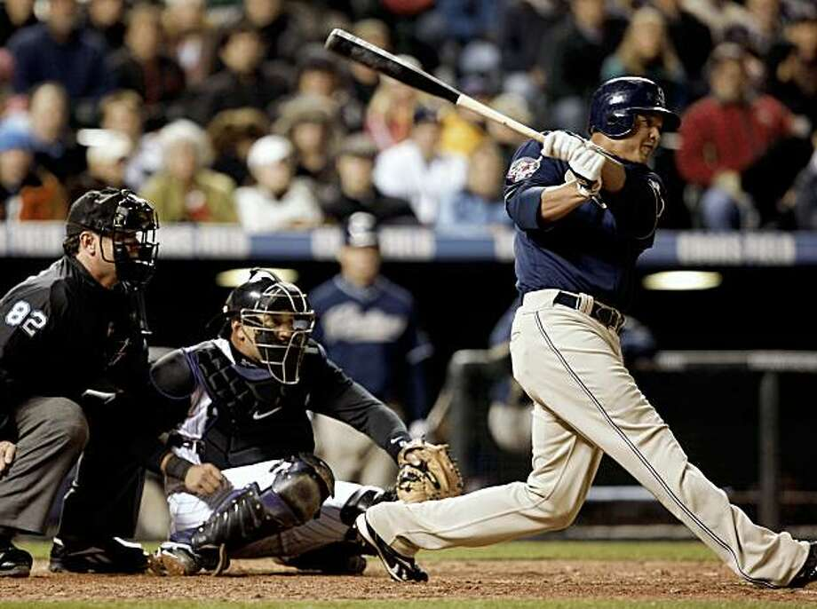San Diego Padres' Will Venable, right, follows the flight of his double to drive in three runs as Colorado Rockies catcher Yorvit Torrealba, center, and home plate umpire Rob Drake, left, look on in the fifth inning of a baseball game in Denver on Wednesday, Sept. 23, 2009. (AP Photo/David Zalubowski) Photo: David Zalubowski, AP