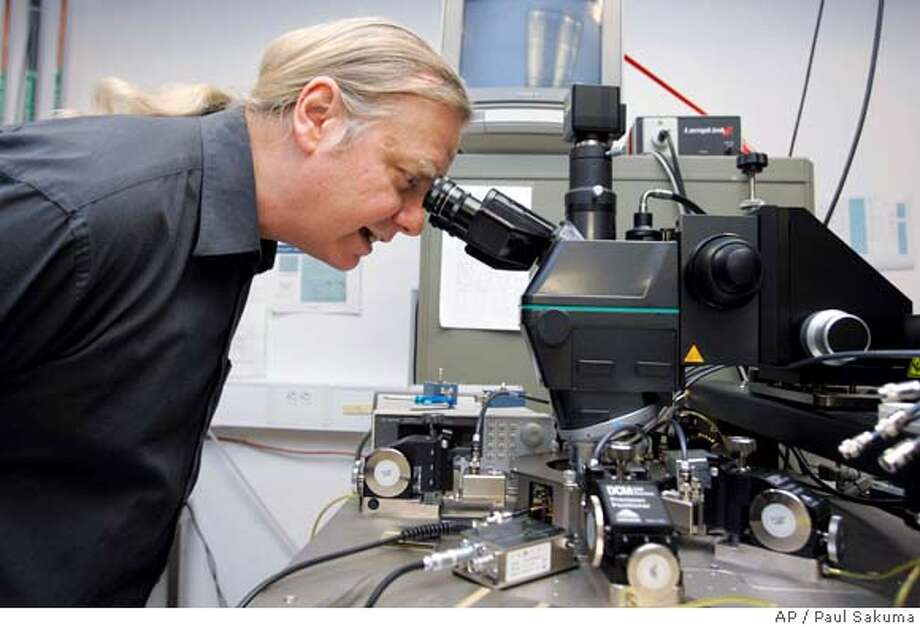 "Hewlett Packard Company senior fellow Stan Williams looks through a special microscope at HP Labs in Palo Alto, Calif., Tuesday, April 29, 2008. Williams and his team were able to create something called a ""memristor,"" which is an new elusive fourth element in electronic circuitry that stores information. It's useful because it remembers data even when the device is turned off, which means it works like a computer memory chip but in far less surface area and using far less power. (AP Photo/Paul Sakuma) Photo: Paul Sakuma"