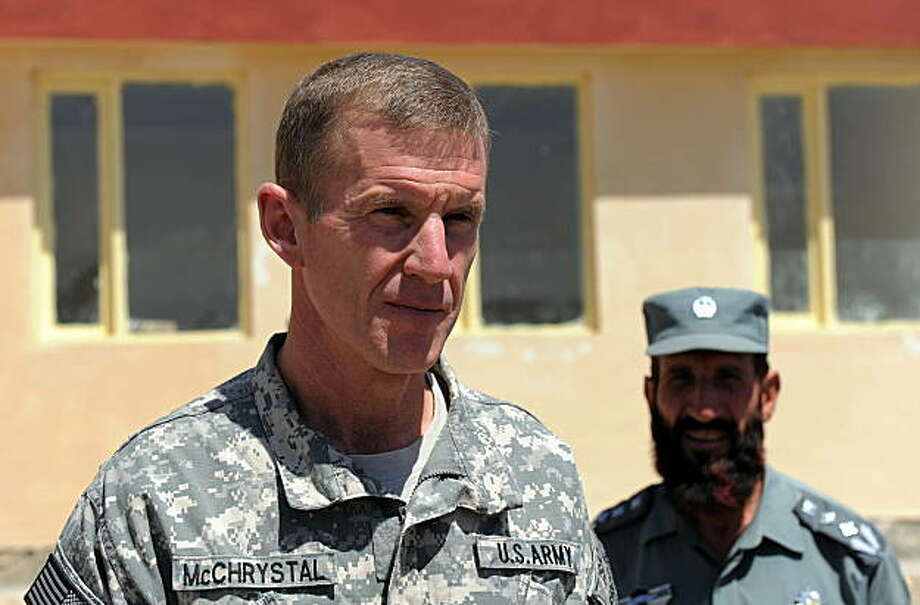 "(FILES) Picture taken on August 21, 2009 shows Commander of the NATO-led International Security Assistance Force (ISAF) US General Stanley McChrystal (L) watched by an Afghan National Police (ANP) officer as he visits their compound at the Baraki Barak district in Logar Province. The top US military commander in Afghanistan has warned that more forces are needed within the next year or the war against the Taliban will be lost, the Washington Post reported on September 21, 2009. General Stanley McChrystal wrote in a classified report: ""Failure to gain the initiative and reverse insurgent momentum in the near-term (next 12 months) -- while Afghan security capacity matures -- risks an outcome where defeating the insurgency is no longer possible."" AFP PHOTO/MANAN VATSYAYANA (Photo credit should read MANAN VATSYAYANA/AFP/Getty Images) Photo: MANAN VATSYAYANA, AFP/Getty Images"