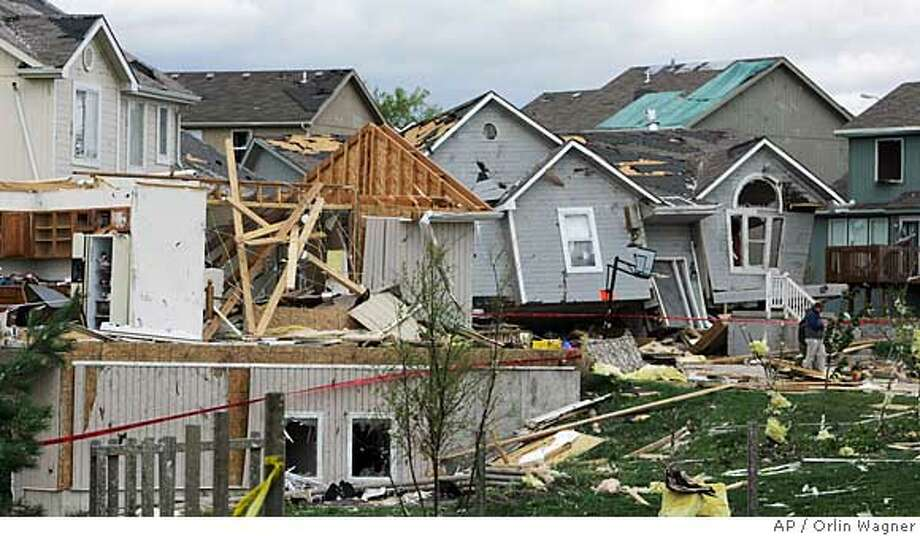 Residents walk through their neighborhood after it was damaged by severe thunderstorm winds in Kansas City, Mo., Friday, May 2, 2008. A powerful storm system packing tornadoes and heavy winds roared across the nation's midsection early Friday, killing at least seven people in Arkansas including a teenager crushed by a tree while she slept. (AP Photo/Orlin Wagner) Photo: Orlin Wagner