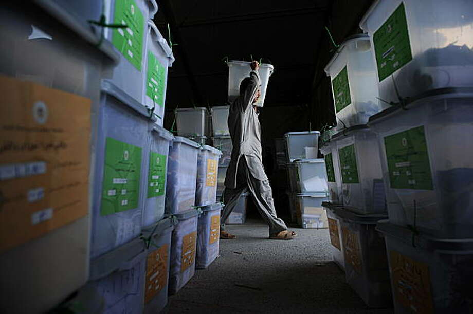 An Afghan man working with the Electoral Complaints Commission (ECC) team carries a ballot box at Independent Elections Commission (IEC) warehouse in Kabul on September 19, 2009. Dusty ballot boxes sit in warehouses across Afghanistan, with monitors worrying that a quarter of the votes locked inside could be fraudulent, most of them cast for incumbent President Hamid Karzai. Despite allegations that vote-rigging was massive and widespread, most of the plastic boxes remain firmly sealed as electoral bodies squabble over how to resolve the crisis, leaving Afghanistan in deadlock.  AFP PHOTO/SHAH Marai (Photo credit should read SHAH MARAI/AFP/Getty Images) Photo: Shah Marai, AFP/Getty Images
