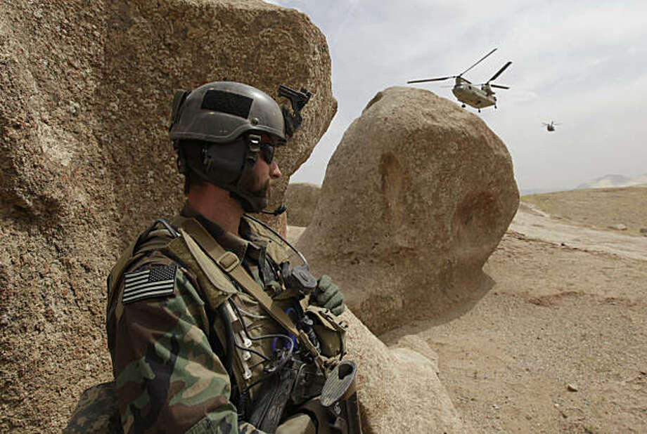 This Sept. 17, 2009 photo shows a Special Forces soldier taking cover as two Chinook Ch-47 helicopters come in for a landing with supplies in the village of Nili, the provincial capital of Day Kundi in central Afghanistan. The team is among only a few U.S. troops to live among Afghans, but there will likely be more. The hope is to push Special Forces teams into villages throughout Afghanistan, giving them the mission of rebuilding and training Afghan police and soldiers rather than hunting insurgents. (AP Photo/Alex Brandon) Photo: Alex Brandon, AP
