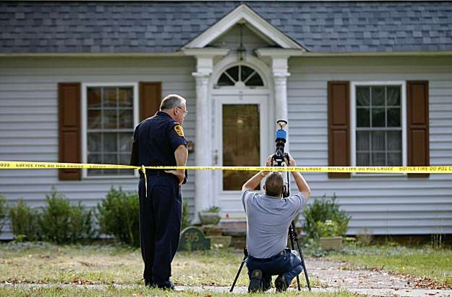 Men with the Virginia State Police photograph 505 First Avenue in Farmville, Va. Saturday, Sept. 19, 2009, during a quadruple homicide investigation. A 20-year-old man suspected of killing four people in the central Virginia college town was arrested at an airport Saturday, where he apparently tried to catch a flight to his home state of California, authorities said. (AP Photo/Richmond Times-Dispatch, Alexa Welch Edlund) Photo: Alexa Welch Edlund, AP