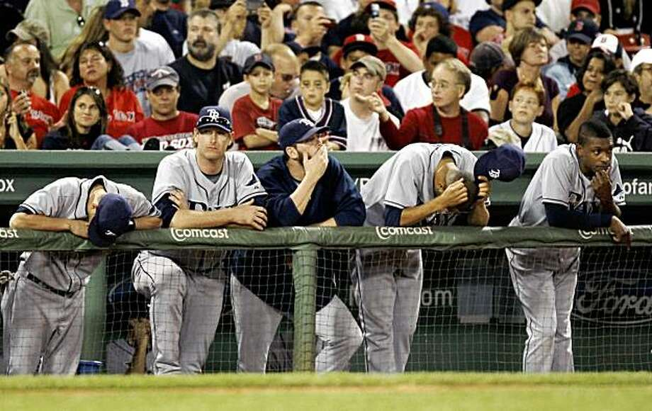 Tampa Bay Rays players lean on the dugout railing during the ninth inning of their 4-0 loss to the Boston Red Sox in game two of a baseball doubleheader at Fenway Park in Boston Sunday, Sept. 13, 2009. The loss was Tampa's 11th straight. (AP Photo/Winslow Townson) Photo: Winslow Townson, AP