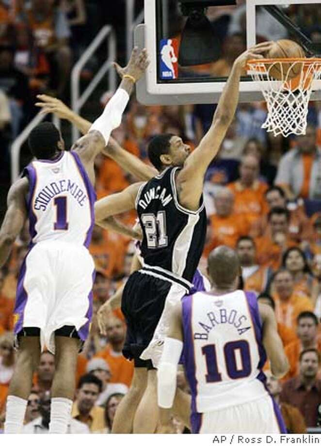San Antonio Spurs' Tim Duncan (21) gets past Phoenix Suns' Amare Stoudemire (1) for a dunk as Suns' Leandro Barbosa (10), of Brazil, looks on in the second quarter in Game 3 of an NBA basketball playoff series Friday, April 25, 2008, in Phoenix. (AP Photo/Ross D. Franklin) Photo: Ross D. Franklin