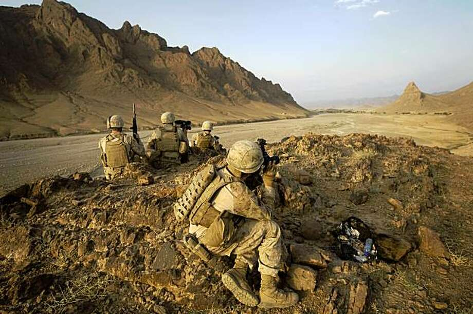 US Marines from 2/3 Fox company keep watch on a hilltop during a patrol in Helmand province, southern Afghanistan, on September 21, 2009. The top US and NATO commander in Afghanistan, General Stanley McChrystal, has warned President Barack Obama in a confidential report that the war against the Taliban could be lost within a year without more troops.  AFP PHOTO/DAVID FURST (Photo credit should read DAVID FURST/AFP/Getty Images) Photo: DAVID FURST, AFP/Getty Images
