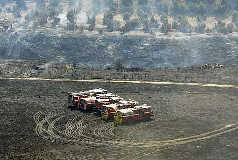 Fire trucks stand ready to move in a burned-over field near groves of trees in the upper Balcom Canyon area as efforts to fight the Guiberson Fire continue outside the Ventura County town of Moorpark, Calif., Wednesday, Sept. 23, 2009.  (AP Photo/Reed Saxon) Photo: Reed Saxon, AP