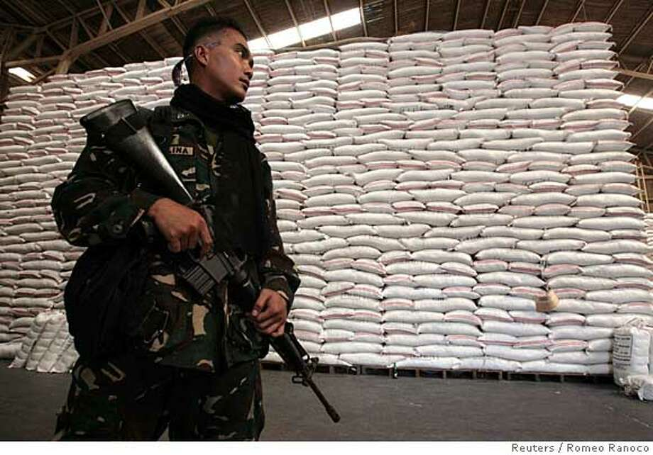 ###Live Caption:A soldier assisting in the delivery and sale of subsidized imported rice sold by the Philippine government to low income groups is seen inside a National Food Authority warehouse in Quezon City, Metro Manila April 23, 2008. Some consumers in Asia are eating less rice or scrimping on already meagre budgets to ensure they can still feed their families a daily helping of the cereal. REUTERS/Romeo Ranoco (PHILIPPINES)###Caption History:A soldier assisting in the delivery and sale of subsidized imported rice sold by the Philippine government to low income groups is seen inside a National Food Authority warehouse in Quezon City, Metro Manila April 23, 2008. Some consumers in Asia are eating less rice or scrimping on already meagre budgets to ensure they can still feed their families a daily helping of the cereal. REUTERS/Romeo Ranoco (PHILIPPINES)  Ran on: 04-25-2008  A soldier helps in the delivery and sale of subsidized imported rice sold by the Philippine government to low-income groups in Quezon City.  Ran on: 04-25-2008###Notes:A soldier assisting in the delivery and sale of subsidized imported rice is seen inside a National Food Authority warehouse in Quezon City###Special Instructions: Photo: ROMEO RANOCO