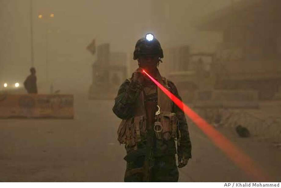 An Iraqi Army soldier uses a flashlight to signal cars to turn off their headlights as a sandstorm envelops central Baghdad, Iraq on Sunday, April 27, 2008. Militants fired a salvo of rockets or mortars at the heavily guarded Green Zone on Sunday, apparently were taking advantage of a sandstorm that blanketed the Iraqi capital Sunday and grounded U.S. helicopters and drones that normally track their activities. (AP Photo/ Khalid Mohammed) Photo: KHALID MOHAMMED
