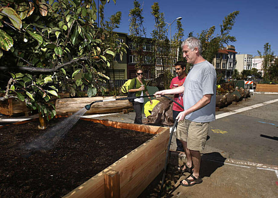 Jeff Goldberg, who worked on the temporary park as a volunteer, waters  the plants in the new park while talking with Pablo Woythaler (center), and Jessica Donohue (left) in San Francisco,  Calif. on Wednesday, September 16, 2009. Photo: Lea Suzuki, The Chronicle