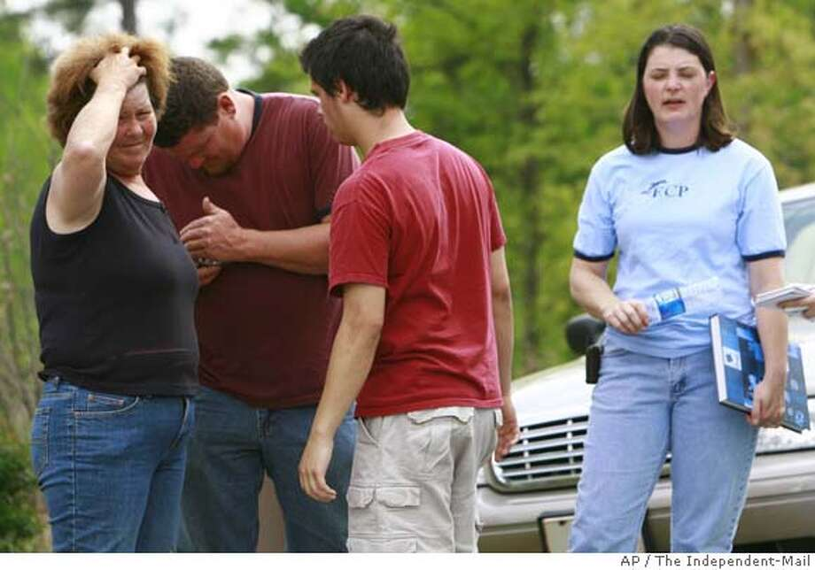 """###Live Caption:From left, Joyce Allen, Garland Blackman, Robbie Funk, and Melissa Funk react after paramedics and police responding to a 911 call discovered the bodies of four people, all shot to death, in and around a home in Easley, S.C. on Saturday, April 26, 2008. Anderson County Sheriff's spokeswoman Susann Griffin said police were looking for 18-year-old Nathaniel Dickson and named him a """"person of interest"""" in the case. (AP Photo/The Independent-Mail,The Independent-Mail)###Caption History:From left, Joyce Allen, Garland Blackman, Robbie Funk, and Melissa Funk react after paramedics and police responding to a 911 call discovered the bodies of four people, all shot to death, in and around a home in Easley, S.C. on Saturday, April 26, 2008. Anderson County Sheriff's spokeswoman Susann Griffin said police were looking for 18-year-old Nathaniel Dickson and named him a """"person of interest"""" in the case. (AP Photo/The Independent-Mail,The Independent-Mail)###Notes:Easley homocide###Special Instructions: Photo: Ken Ruinard"""