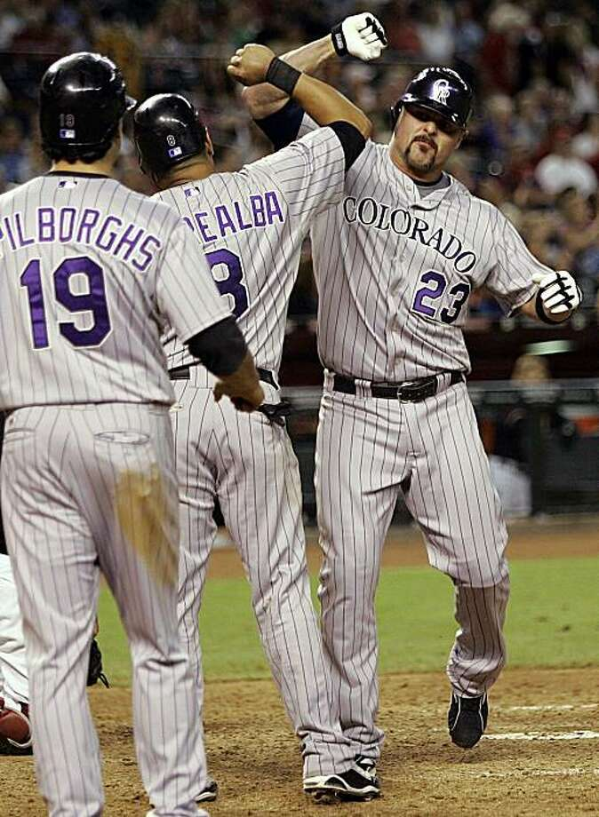 Colorado Rockies' Jason Giambi (23) is congratulated by teammates Yorvit Torrealba and Ryan Spilborghs (19) after Giambi hit a three-run pinch-hit home run against the Arizona Diamondbacks during the ninth inning of a baseball game Saturday, Sept. 19, 2009, in Phoenix. (AP Photo/Matt York) Photo: Matt York, AP