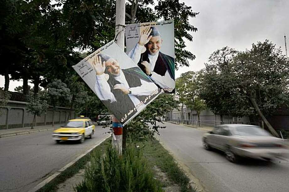 Election posters of incumbent Afghan president Hamid Karzaiare are seen on a street, in Kabul, Afghanistan, Wednesday, Sept. 16, 2009. Afghanistan's election commission released preliminary vote totals Wednesday showing President Hamid Karzai with 54.6 percent of the vote in the first full results to be released since the country's Aug. 20 election(AP Photo/Manish Swarup) Photo: Manish Swarup, AP