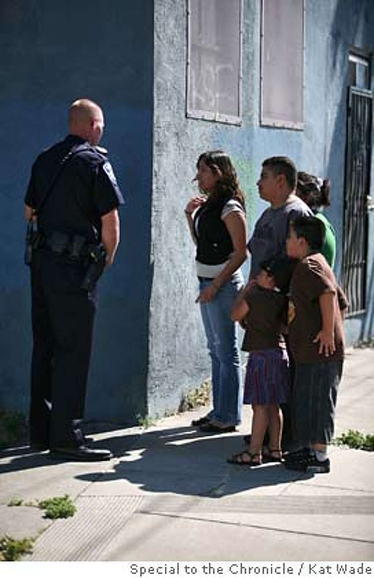 ###Live Caption:From left, Oakland police officer Frank Petersen, stops Marible Melendez, 14, and her family as they try to go home past the scene where a suspect was killed at 29th Avenue and East 7th Street in Oakland, Calif. on Saturday, April 26, 2008. Photo by Kat Wade / Special to the Chronicle###Caption History:From left, Oakland police officer Frank Petersen, stops Marible Melendez, 14, and her family as they try to go home past the scene where a suspect was killed at 29th Avenue and East 7th Street in Oakland, Calif. on Saturday, April 26, 2008. Photo by Kat Wade / Special to the Chronicle###Notes:Frank Petersen, stops Marible Melendez, 14, (CQ< subjects) The others left before they could give their names I heard that the dead suspect man hijacked a car and had the owner, an old-man in handcuffs.###Special Instructions:Mandatory Credit for photographer and S.F. CHRONICLE/No Sales - mags out