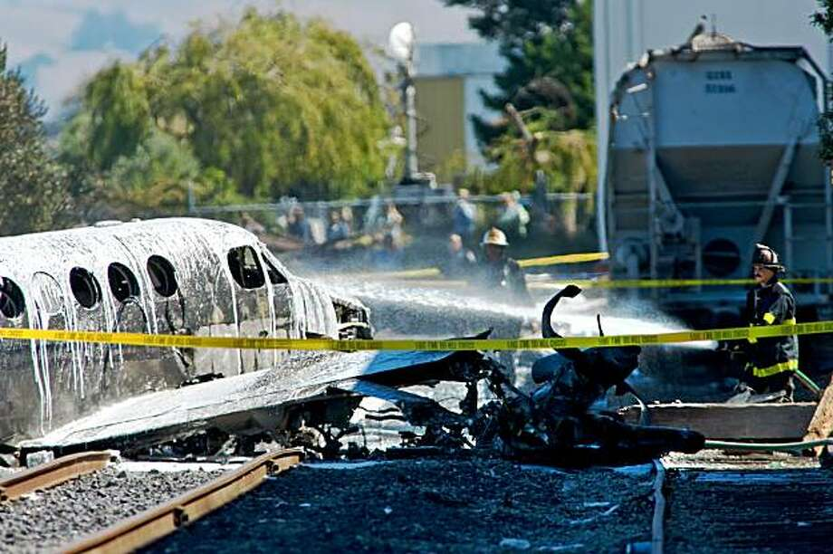 Firefighter spays foam on the wreckage of a twin engine Beechcraft King Air that crashed on take off as it sits behind an industrial park adjacent to Hayward Airport in Hayward, California on Sep. 16, 2009. Photo: Peter DaSilva, Special To The Chronicle