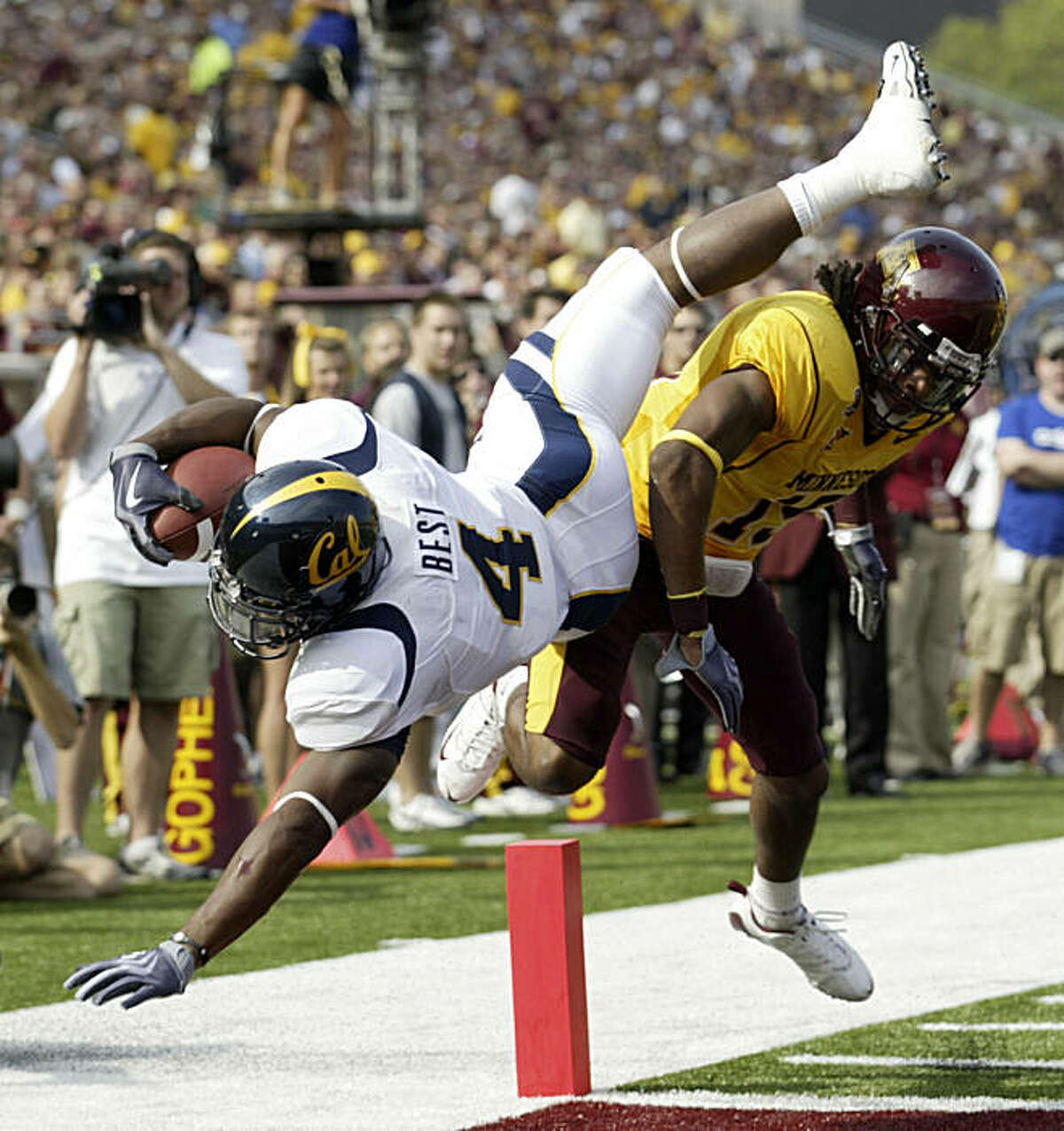 California tailback Jahvid Best (4) is upended at the goal by Minnesota cornerback Traye Simmons (15) as he scores on a 33-yard touchdown run during the first half of a NCAA football game, Saturday, Sept. 19, 2009 in Minneapolis. (AP Photo/Paul Battaglia)