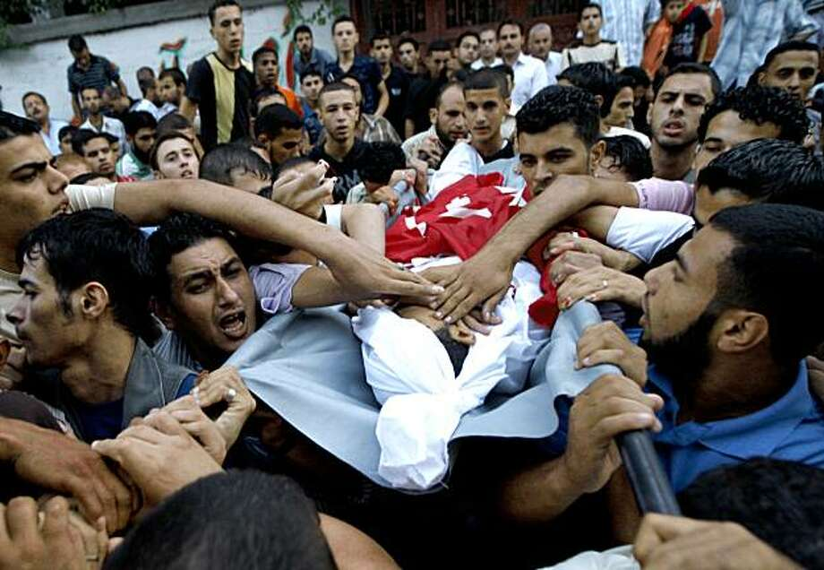 Palestinian mourners carry the body of Mahmoud Nsairm, a militant member of the Popular Front for Liberation of Palestine movement (PFLP), during his funeral in Jabaliya, northern Gaza Strip, Sunday, Sept. 20, 2009.  A Palestinian Health Ministry official says Israeli forces have killed two Palestinian militants and wounded three in an incident along the Gaza border. (AP Photo/Khalil Hamra) Photo: Khalil Hamra, AP