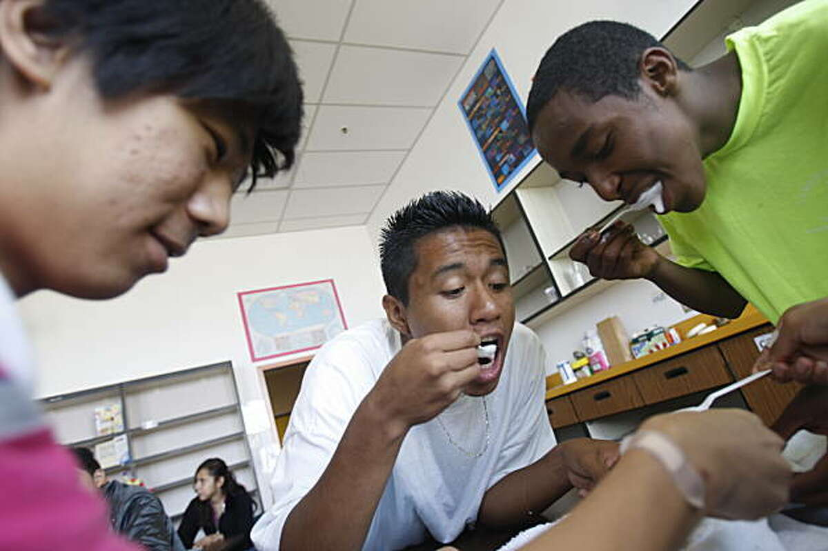 Johnny,16 (l to r); Osmar 14 and Medhanie, 15, take a taste test of their biology project - ice cream - as part of their introduction to lab reports during biology class at International High School in San Francisco, Calif. on Tuesday, September 1, 2009.