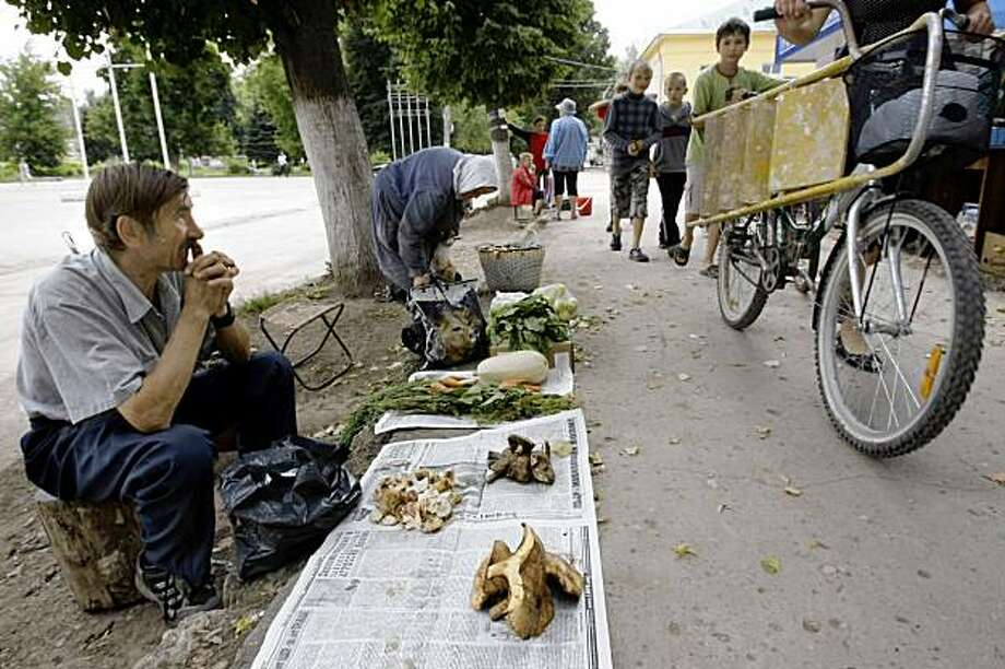 This Aug. 5, 2009 photo shows a man selling mushrooms in downtown Yasnogorsk, Russia. The Yasnogorsk Machine-Building Factory stamped out thousands of pounds of steel and iron into parts for wagons, pumps and locomotives for Russia's mining industry, but the factory that this town grew up around, is on its last breath, choked by a global recession that has shaken Russia to the core. (AP Photo/Misha Japaridze) Photo: Misha Japaridze, AP
