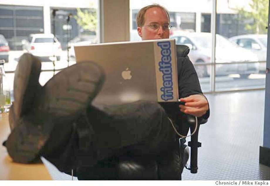 While his colleagues discuss new ideas, Paul Buchheit, one of 4 founders of a startup called friendfeed, works on from his laptop at an inexpensive Ikea desk on Monday April, 21, 2008 in Mt. View, Calif. Friendfeed which only has a handful of employees is an example of how startups of today are operating on a much small scale that many failed startups of old. Photo by Mike Kepka / San Francisco Chronicle Photo: Kepka, Mike