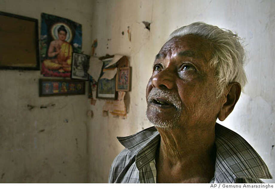**ADVANCE FOR SUNDAY, APRIL 20** P.P. James reacts after looking at wedding pictures hung on the wall at his uncle's house where he grew up in Hipauwa, about 90 kilometers (56 miles) northeast of Colombo, Sri Lanka on Friday, Feb. 29, 2008. (AP Photo/Gemunu Amarasinghe) Photo: Gemunu Amarasinghe