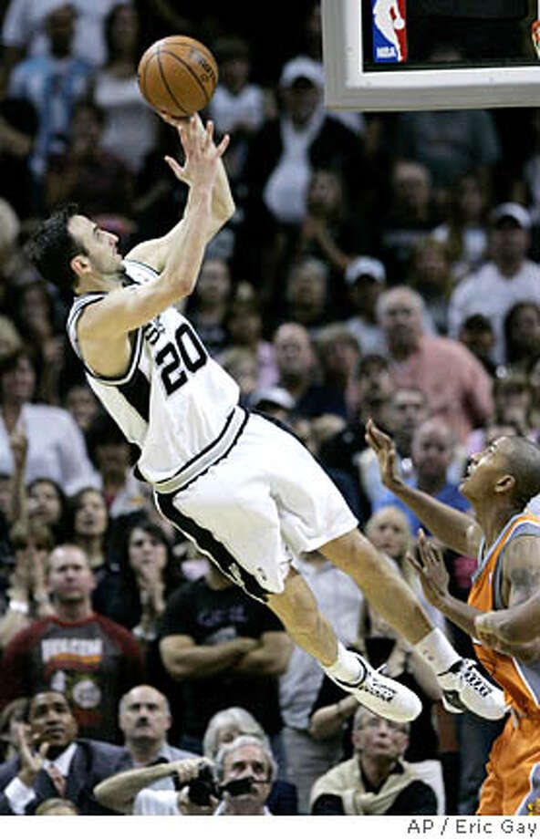 San Antonio Spurs guard Manu Ginobili, left, of Argentina, shoots the game-winning shot over Phoenix Suns guard Raja Bell, right, during the second overtime in Game 1 of their Western Conference playoff basketball series in San Antonio, Saturday, April 19, 2009. San Antonio won 117-115. (AP Photo/Eric Gay) Photo: Eric Gay