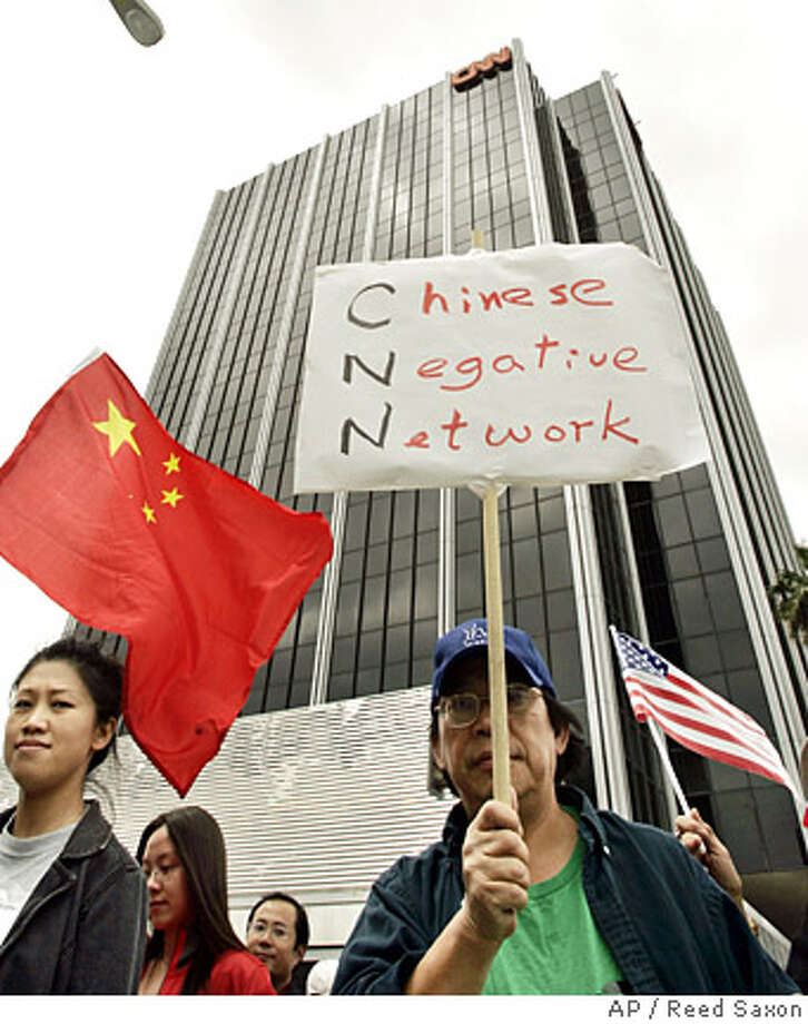 "Chinese-Americans and others rally outside CNN's Hollywood office to demand the firing of commentator Jack Cafferty for calling China's goods ""junk"" and its leaders a ""bunch of goons and thugs,"" in Los Angeles Saturday, April 19, 2008. A crowd estimated by police at 2,000 to 5,000 gathered, chanting ""Cafferty, Fire,"" and singing Chinese songs. The crowd was peaceful and no arrests were made, police Sgt. David Torres said. (AP Photo/Reed Saxon) Photo: Reed Saxon"
