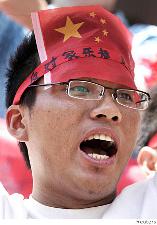 "A man puts on a Chinese national flag and a banner reading ""oppose Carrefour"" during a demonstration against Carrefour supermarket and French goods on a street in Kunming, Yunnan province April 19, 2008. Chinese official media have sought to temper nationalist calls to boycott foreign businesses accused of backing Tibetan independence, urging angry citizens to focus on economic development. REUTERS/Stringer (CHINA). CHINA OUT. NO COMMERCIAL OR EDITORIAL SALES IN CHINA.  Ran on: 04-20-2008  A protester wears a Chinese flag and headband reading &quo;Oppose Carrefour&quo; at a demonstration against the French supermarket chain. Photo: STRINGER SHANGHAI"