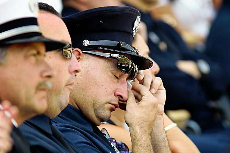 Firefighters gather at a public memorial service at Dodger Stadium for two Los Angeles County firefighters who died while fighting the 250-square-mile Station fire on September 12, 2009 in Los Angeles, California. Captain Ted Hall and firefighter specialist Arnie Quinones died August 30 when their fire truck rolled 800 feet down a hillside as they retreated from flames near Mount Gleason. Photo: David McNew, Getty Images