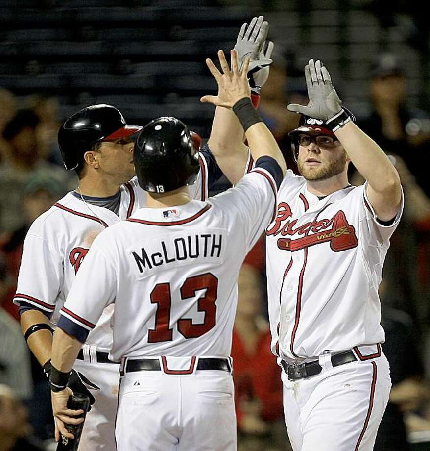 Atlanta Bravers' Brian McCann, right, celebrates with teammates Nate McLouth (13) and Martin Prado after hitting a three-run home run in the fifth inning of a baseball game against the New York Mets on Thursday, Sept. 17, 2009, in Atlanta. (AP Photo/John Bazemore) Photo: John Bazemore, AP