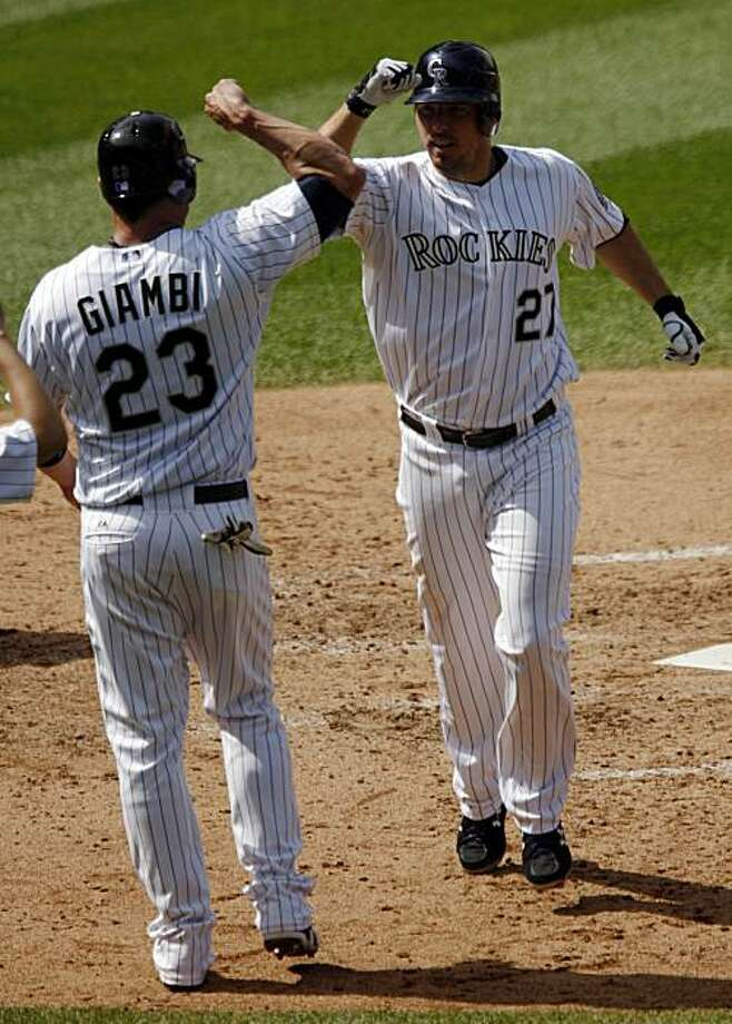 Colorado Rockies' Jason Giambi, left, congratulates teammate Garrett Atkins after Atkins' two-run home run against the Cincinnati Reds in the third inning of the Rockies' 5-1 victory in a baseball game in Denver on Thursday, Sept. 10, 2009. (AP Photo/David Zalubowski) Photo: David Zalubowski, AP