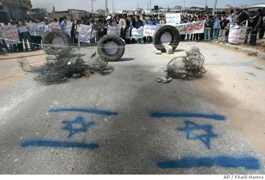 """###Live Caption:Palestinian school children stand on a blocked road with Israeli flags sprayed on the asphalt as they hold a protest calling for a break in the siege on Gaza Strip, in the town of Beit Hanoun, northern Gaza Strip, Monday, April 21, 2008. Hamas would accept a Palestinian state on only part of the land it claims and would grant Israel a 10-year """"hudna,"""" or truce, as an implicit proof of recognition if Israel withdraws from those areas, the Palestinian militant group's leader said Monday. (AP Photo/Khalil Hamra)###Caption History:Palestinian school children stand on a blocked road with Israeli flags sprayed on the asphalt as they hold a protest calling for a break in the siege on Gaza Strip, in the town of Beit Hanoun, northern Gaza Strip, Monday, April 21, 2008. Hamas would accept a Palestinian state on only part of the land it claims and would grant Israel a 10-year """"hudna,"""" or truce, as an implicit proof of recognition if Israel withdraws from those areas, the Palestinian militant group's leader said Monday. (AP Photo/Khalil Hamra)###Notes:###Special Instructions: Photo: KHALIL HAMRA"""