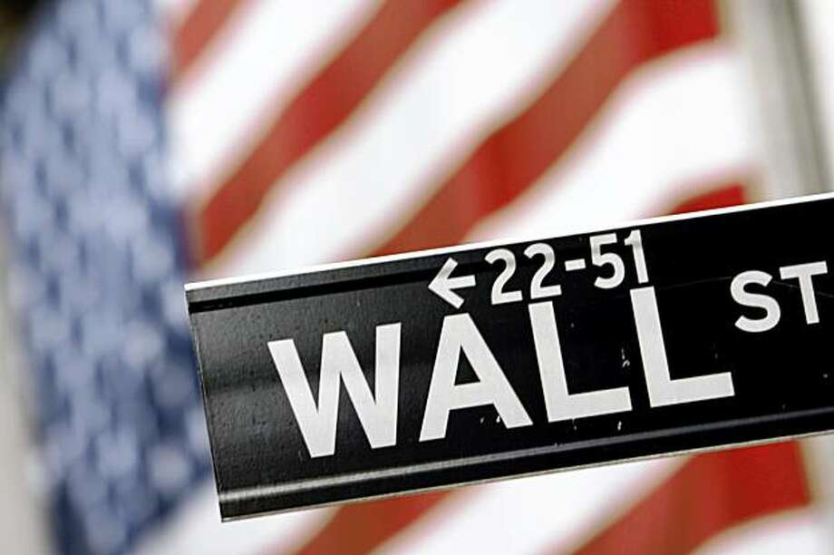 FILE - In this Sept. 25, 2008 file photo, a Wall St. street sign is shown in front of the American flag hanging on the New York Stock Exchange in New York. Stocks fell sharply Tuesday, Sept. 1, 2009, giving up earlier gains after the Institute for Supply Management said its index of manufacturing activity rose to 52.9 in August, up from 48.9 in July and well above the reading of 50.5 analysts had been expecting. (AP Photo/Mary Altaffer, file) Photo: Mary Altaffer, AP
