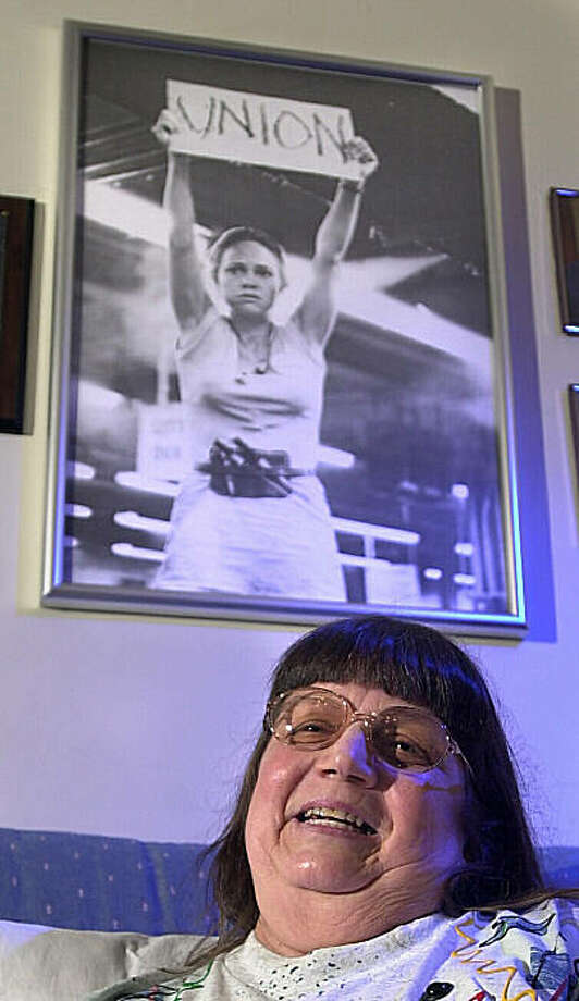 "FILE - In this Aug. 16, 2001 file photo, a photo of Sally Fields in the movie ""Norma Rae"" hangs in Crystal Lee Sutton's home in Burlington, NC. The character in the movie was based on Sutton, who helped organize workers at the J.P. Stevens plant in Roanoke Rapids. Sutton died Friday in Burlington Friday Sept. 11, 2009. She was 68. (AP Photo/News & Record, Joseph Rodriguez, File) Photo: Joseph Rodriguez, AP"