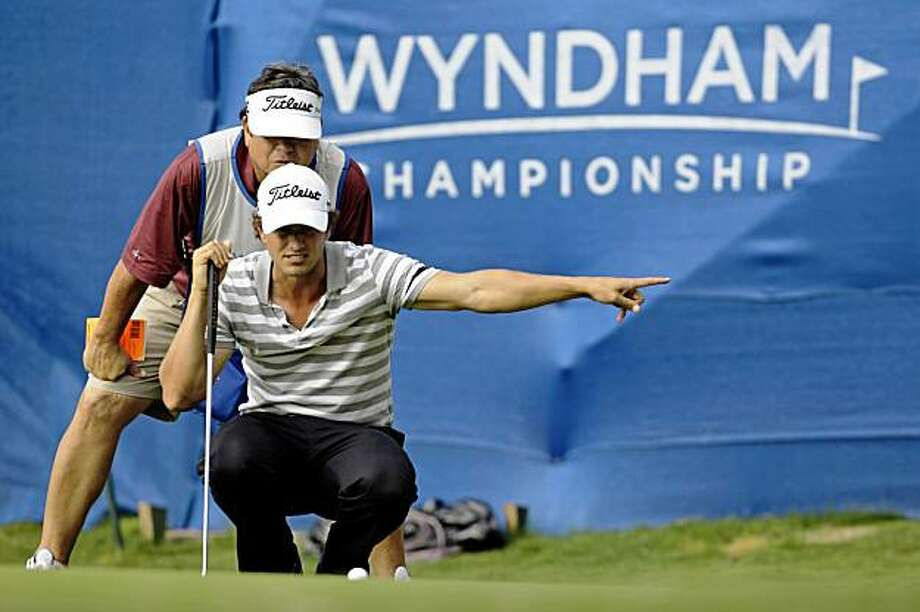 Adam Scott, of Australia, lines up a putt during the continuation of the weather delayed first round of the Wyndham Championship PGA golf tournament at Sedgefield Country Club in Greensboro, N.C., Friday, Aug. 21, 2009. (AP Photo/Chuck Burton) Photo: Chuck Burton, AP