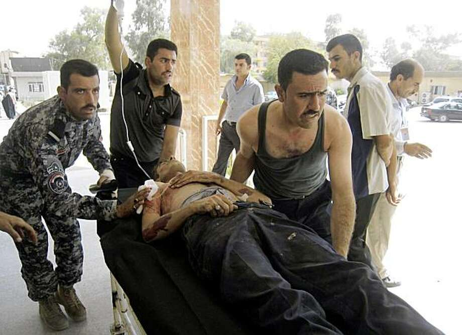 A wounded policeman is rushed to the hospital in Kirkuk, 290 kilometers (180 miles) north of Baghdad, Tuesday, Sept. 8, 2009. A roadside bomb struck a police patrol near the town of Daqouq, killing two policemen and wounding three others, Kirkuk police said. Photo: Emad Matti, AP